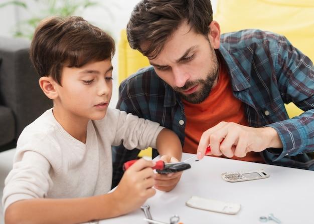Vater und sohn, die ein telefon reparieren