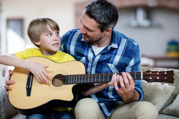 Vater und sohn, die eine gitarre spielen
