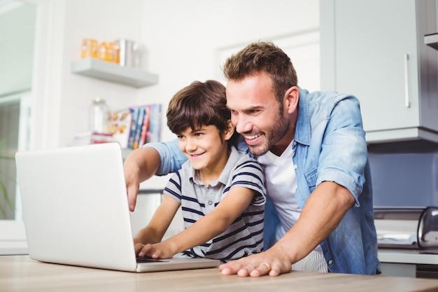 Vater und sohn, die einen laptop verwenden