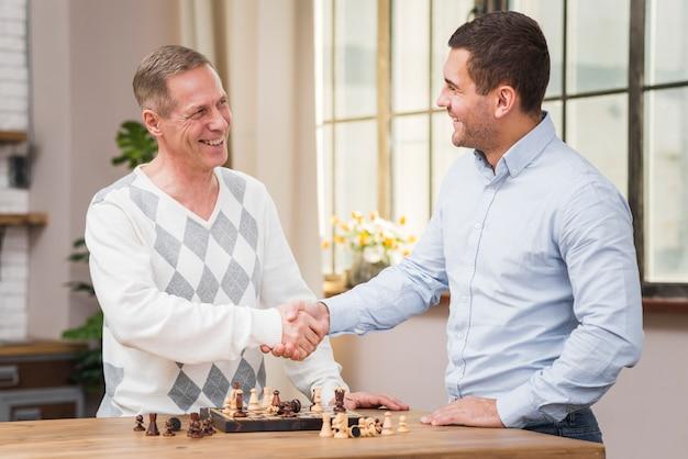 Vater und sohn, die hand nach einem schachspiel rütteln