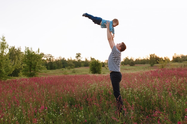 Vater und sohn, die im frühjahr feld zur sonnenuntergangzeit spielen. leute, die spaß auf dem feld haben.