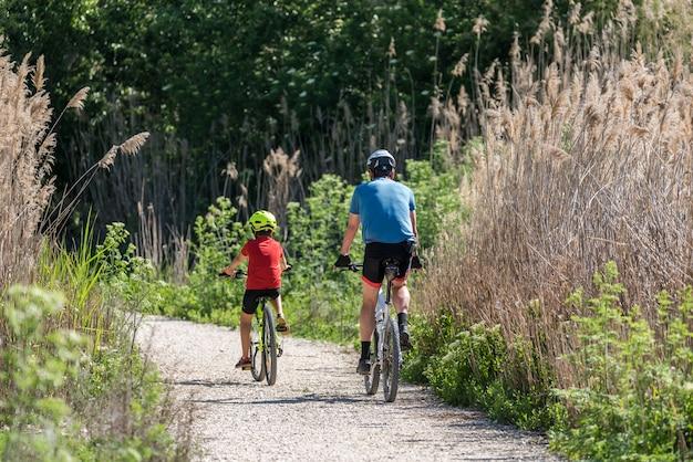 Vater und sohn, die mit dem fahrrad sport treiben