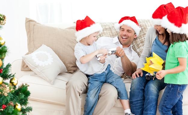 Vater und sohn, die mit einem cracker auf dem sofa spielen