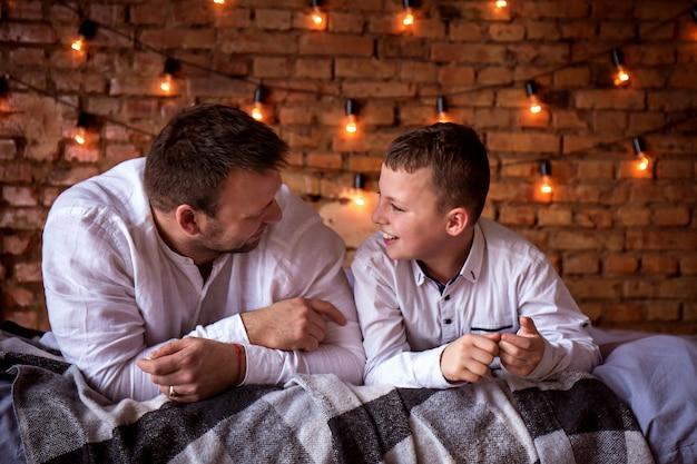Vater und sohn, die zu hause reden, liegen im bett