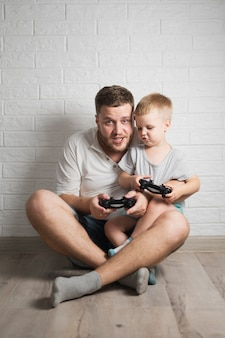 Vater und sohn, die zusammen mit steuerknüppel spielen