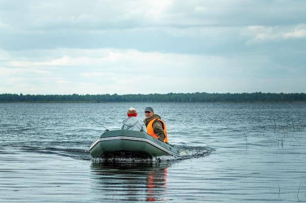 Vater und sohn fahren mit einem motorboot auf dem see.