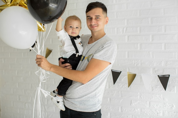Vater und sohn feiern den 1. geburtstag zusammen lachen und lächeln mit luftballons, einem schokoriegel.