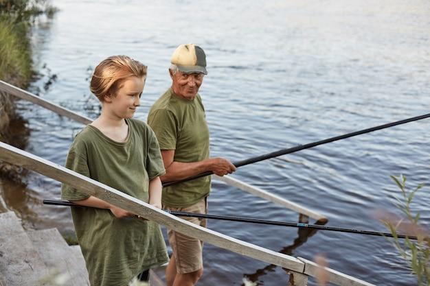 Vater und sohn fischen auf holztreppen, die zum wasser führen