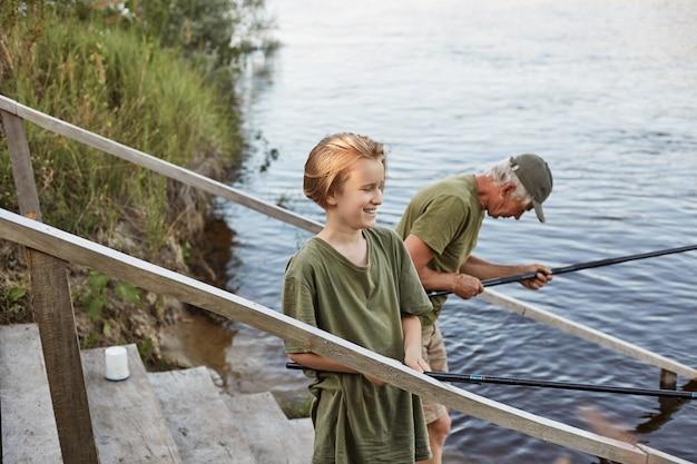 Vater und sohn fischen zusammen und stehen auf holztreppen, die zum wasser führen