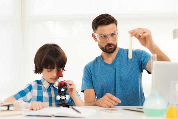 Vater und sohn führen zu hause chemische experimente durch.