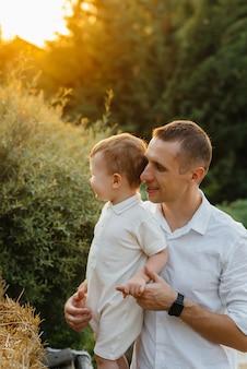 Vater und sohn gehen im park bei sonnenuntergang. glück. liebe