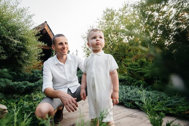 Vater und sohn gehen im park bei sonnenuntergang. glück. liebe.