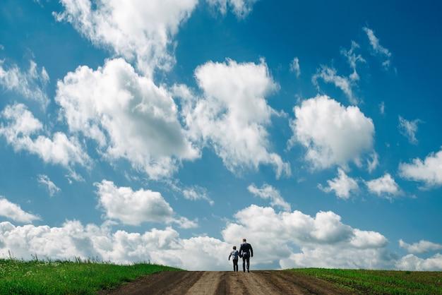 Vater und sohn gehen im sommer außerhalb der stadt spazieren