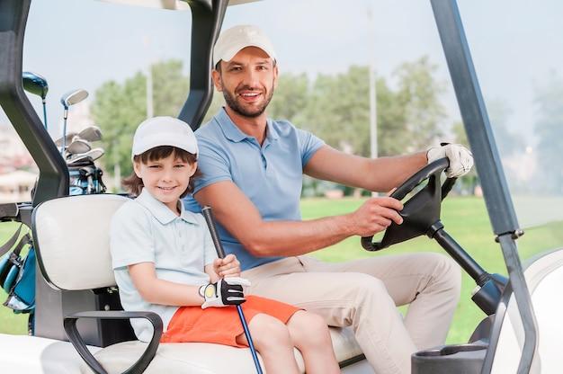 Vater und sohn im golfwagen. lächelnder kleiner junge, der im golfwagen sitzt, während sein vater ihn fährt