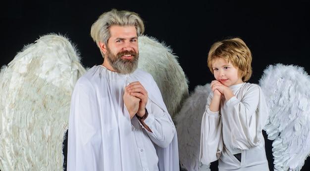Vater und sohn in engelskostümen. valentinstag. glückliche familie mit weißen flügeln.