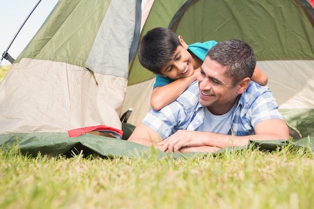 Vater und sohn in ihrem zelt in der landschaft an einem sonnigen tag