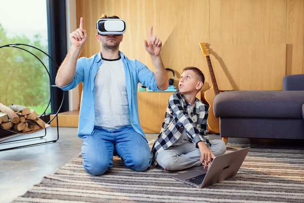 Vater und sohn in virtual-reality-headsets spielen zu hause mit gamepads