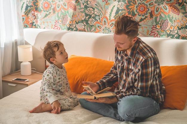 Vater und sohn lasen zusammen ein buch, lächelten und umarmten sich. familienurlaub und zusammensein