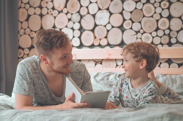 Vater und sohn lasen zusammen ein buch, lächelten und umarmten sich