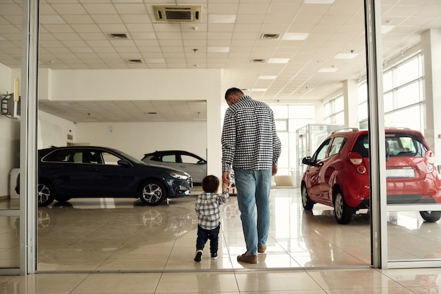 Vater und sohn laufen auf der großen automesse herum und überlegen sich neue automodelle.