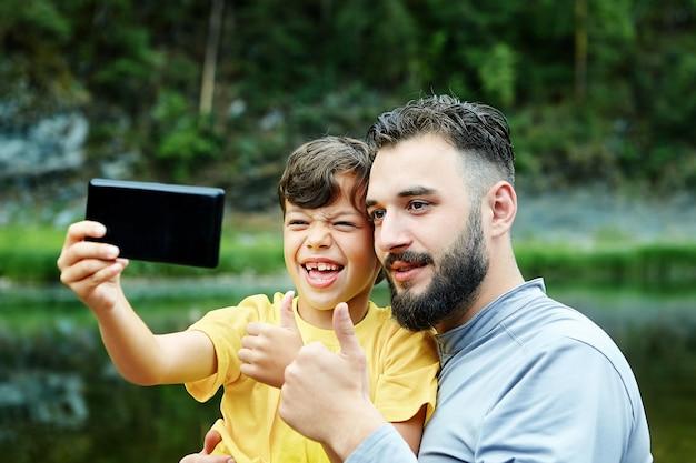 Vater und sohn machen ein gemeinsames selfie, sie fotografieren sich am ufer des wilden flusses, kamera im handy.