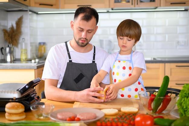 Vater und sohn machen einen leckeren hamburger