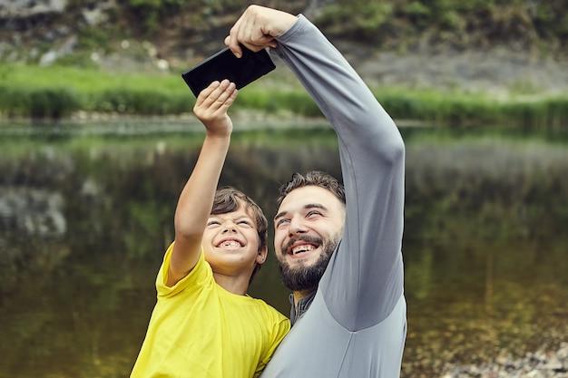 Vater und sohn machen selfie mit fluss im hintergrund im wald, sie lächeln in die kamera.