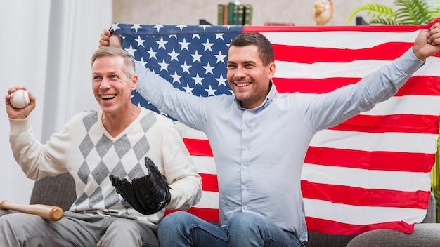 Vater und sohn mit baseballmaterial und -flagge