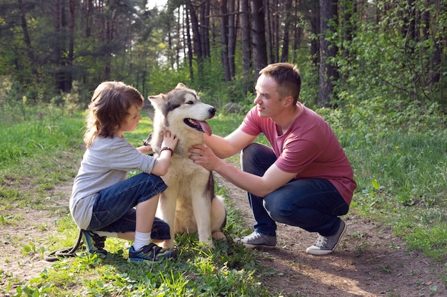 Vater und sohn mit ihrem hund malamute auf einem spaziergang im wald