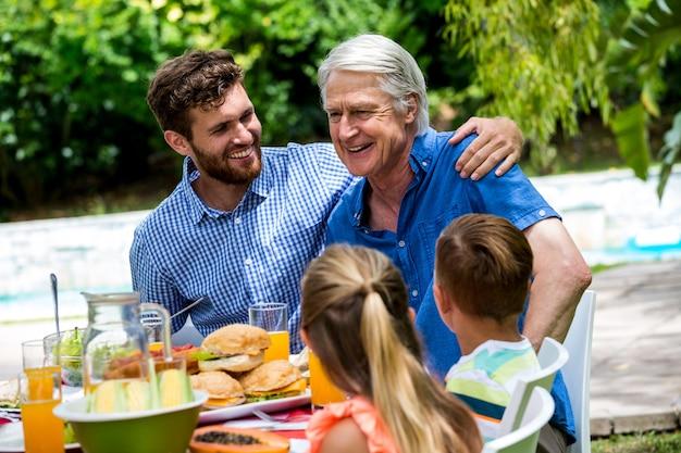 Vater und sohn mit kindern am esstisch im rasen