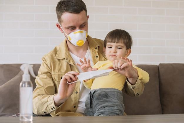 Vater und sohn mit medizinischen masken