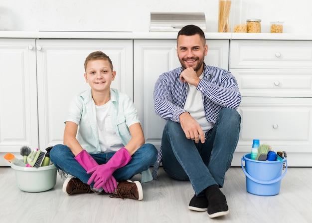 Vater und sohn posieren während der hausreinigung mit produkten