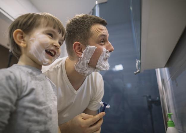 Vater und sohn rasieren sich im badezimmer die bärte