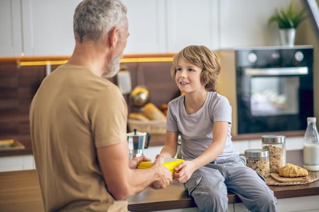 Vater und sohn. reifer mann im beige t-shirt und sein sohn in der küche zu hause
