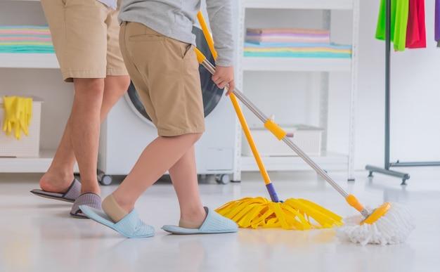 Vater und sohn reinigen den hausboden zusammen mit gelbem mp, geschlossener schuss mit nicht erkennbarem gesicht in einem farbenfrohen raum.