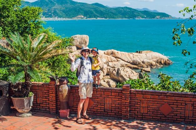 Vater und sohn reisende betrachten hon chong kap, gartenstein, beliebte touristenziele in nha trang. vietnam