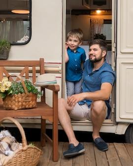 Vater und sohn schauen weg, während sie im wohnwagen sitzen