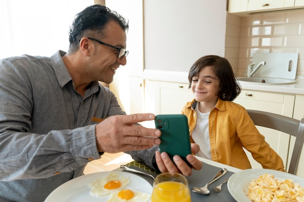 Vater und sohn schauen zu hause auf ein smartphone