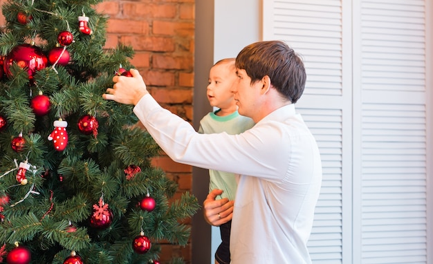 Vater und sohn schmücken den weihnachtsbaum im wohnzimmer