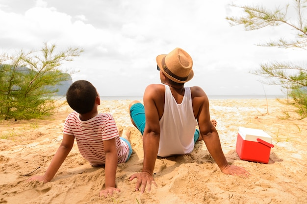 Vater und sohn sind glücklich für picknick am strand