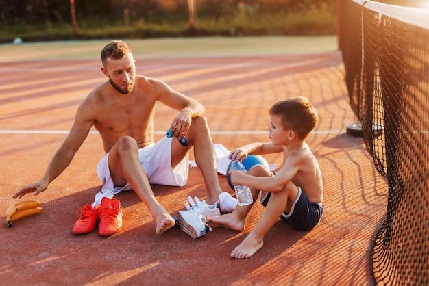Vater und sohn sitzen auf dem platz und ziehen sich für das training an. sommerzeit am morgen.