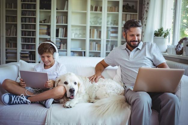 Vater und sohn sitzen auf dem sofa und benutzen digitales tablet und laptop