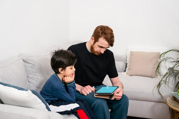 Vater und sohn sitzen auf dem sofa und schauen in tablette