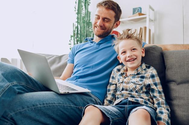 Vater und sohn sitzen auf der couch und schauen sich etwas auf dem laptop an
