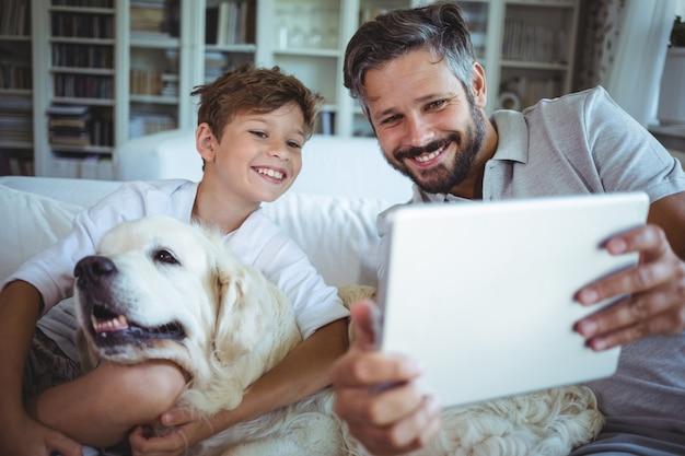 Vater und sohn sitzen auf sofa mit hund und verwenden digitales tablet