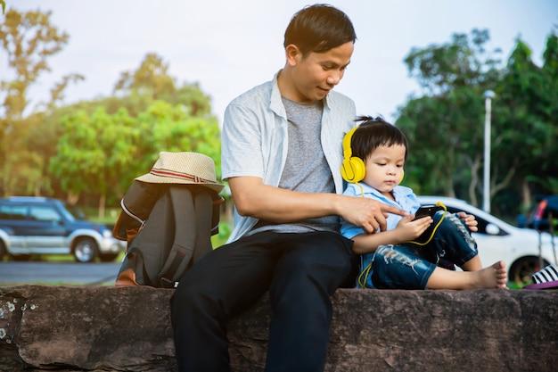 Vater und sohn sitzen und schauen dem telefon im park zu