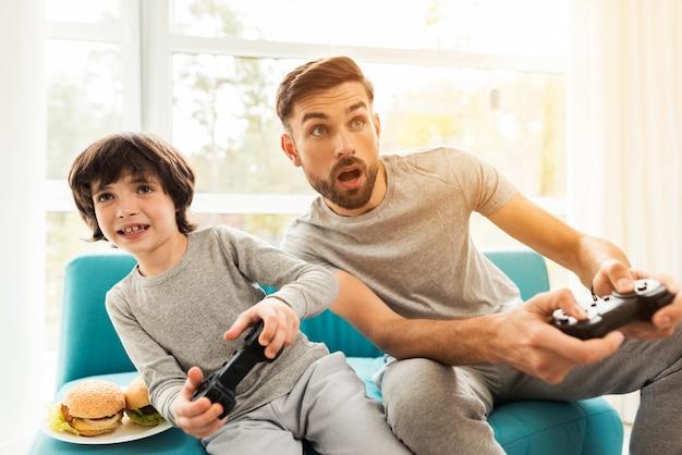 Vater und sohn sitzen und spielen auf der konsole.