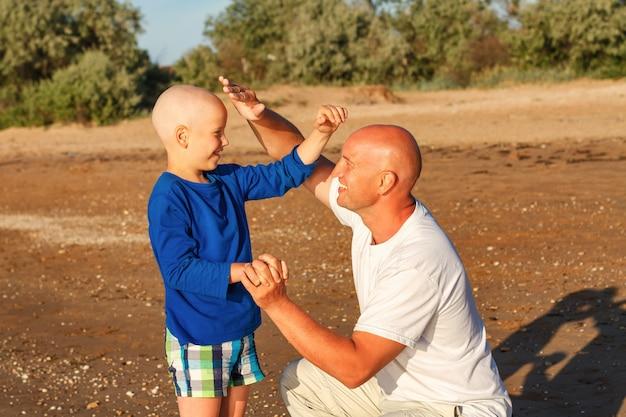 Vater und sohn spielen am meer, glückliche familie