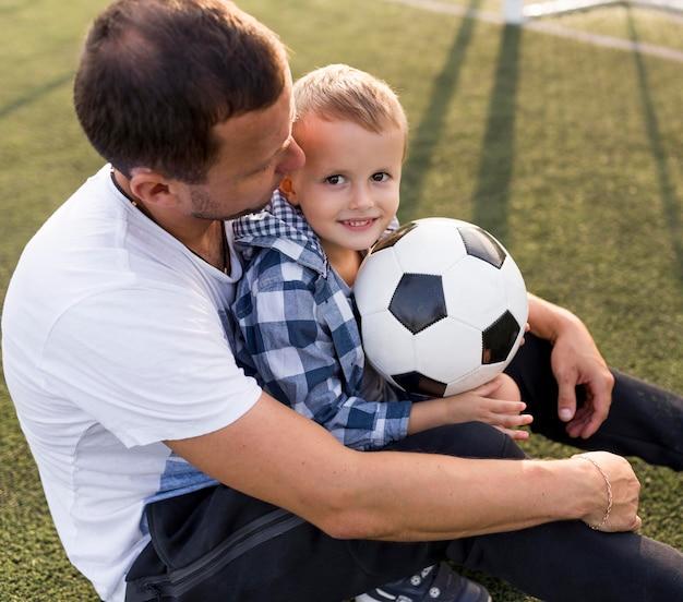 Vater und sohn spielen auf dem fußballplatz hohe ansicht