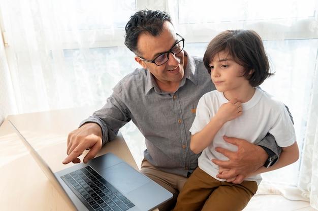 Vater und sohn spielen etwas auf einem laptop